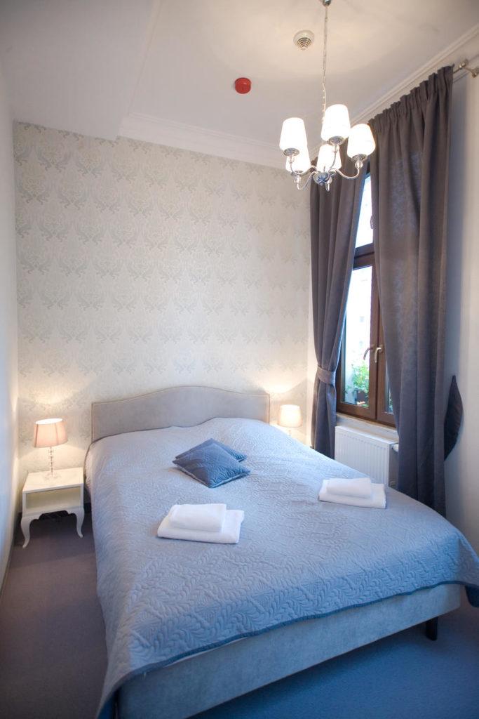 duże łóżko w dwupokojowym apartamencie